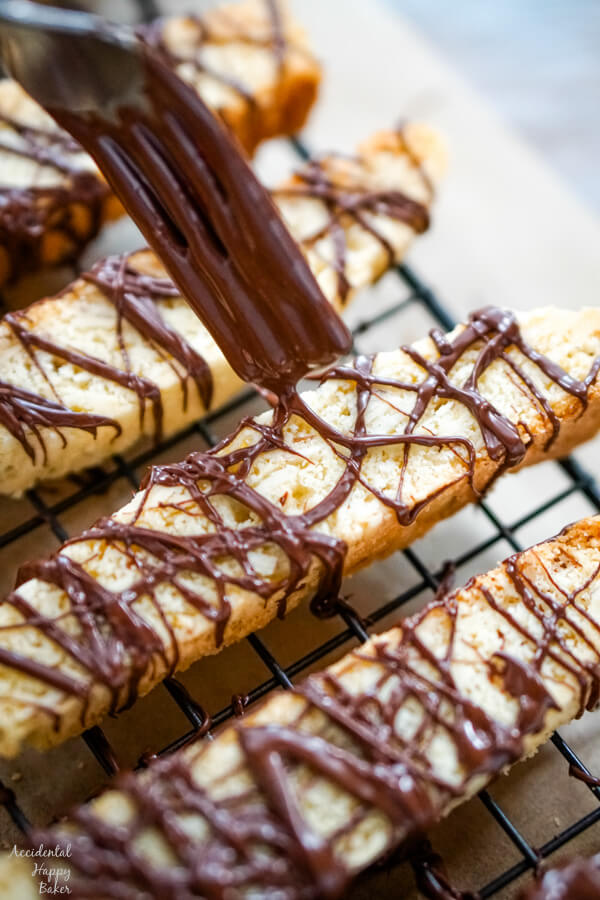 Drizzle the melted chocolate over the cooled biscotti cookies.