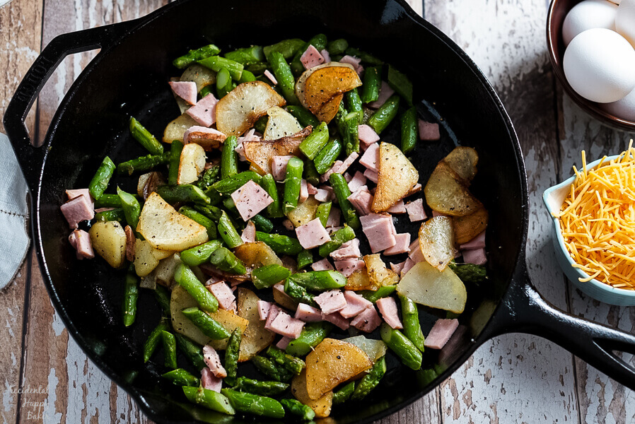 Potatoes, Ham, and Asparagus are cooked in a cast iron skillet before adding the eggs.