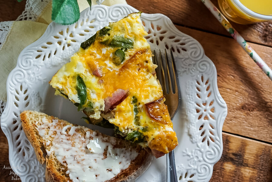 Ham, Asparagus, and Potato Frittata on a plate next to buttered toast and juice.