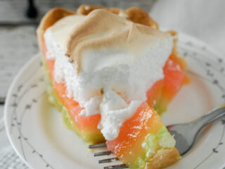 A bite of rainbow lemon meringue pie rests on a fork, showing the layers of colored filling.