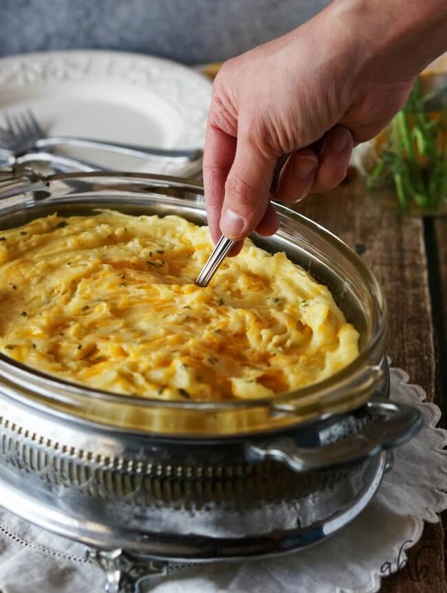 Creamy and fluffy mashed potatoes are taken to the next level of delicious with the addition of sharp cheddar cheese for a side dish everyone will love. Recipe on www.accidentalhappybaker.com @AHBamy