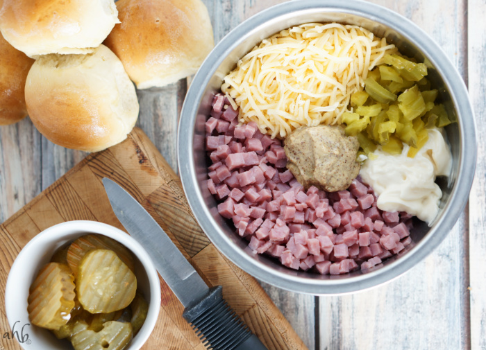 Ham, deli mustard, swiss cheese, mayo, and pickles in a mixing bowl ready to be stirred.