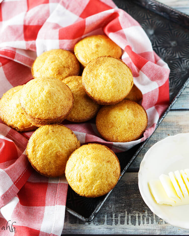 A tray of baked corn muffins next to a stick of butter.