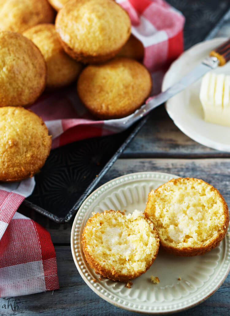 A cornbread muffin sliced with melted butter in the center.