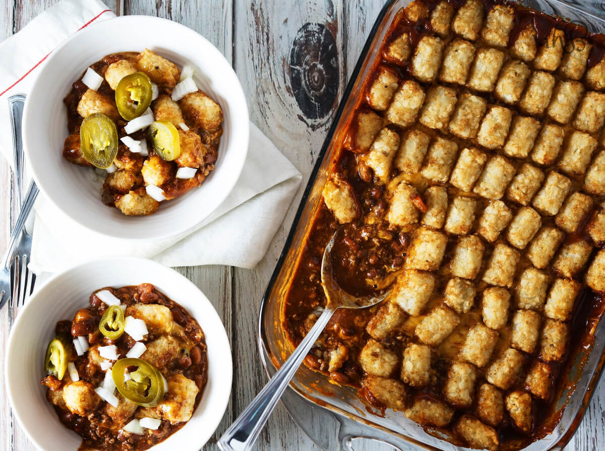 Two servings of Chili Cheese Tater Tot Casserole next to a casserole pan.