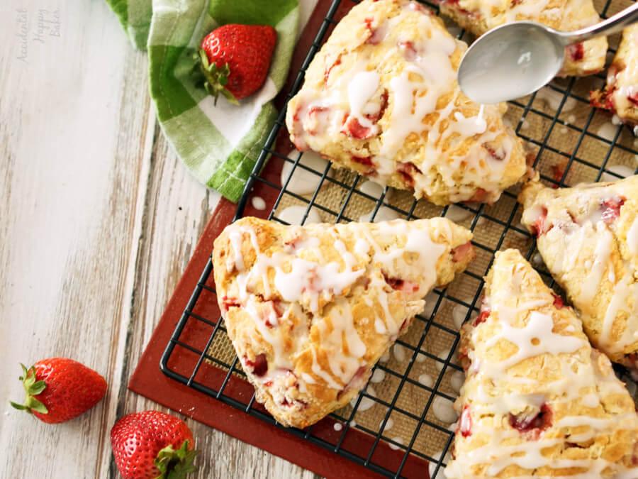 Drizzling lemon glaze over strawberry scones.