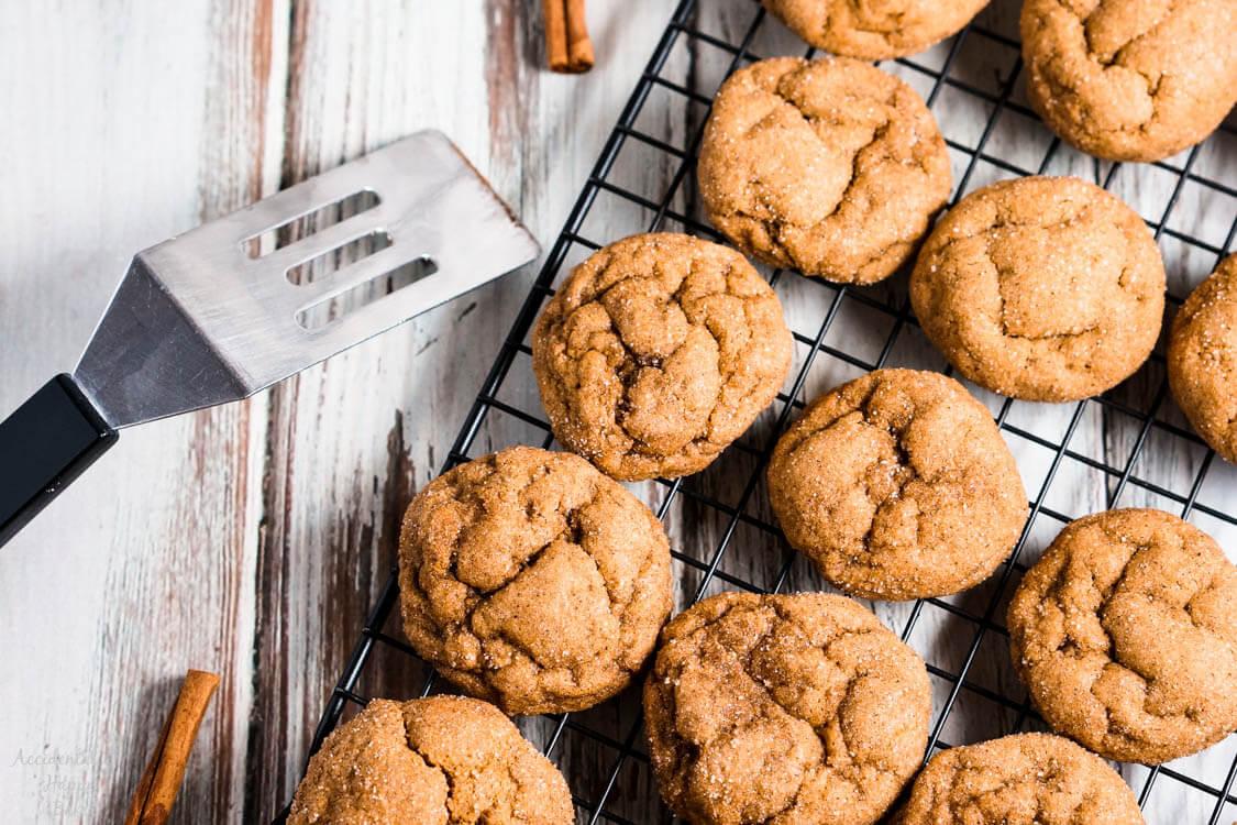 Several pumpkin gingersnap cookies set on a cooling rack.