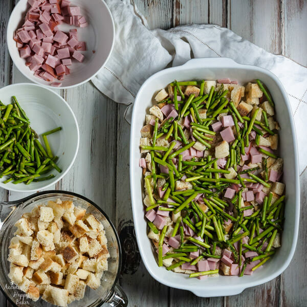 Layers of English muffins, ham, asparagus and cheese are drenched in eggs, Hollandaise mix and half and half for a hearty breakfast casserole that works great anytime of year. #ham #asparagus #breakfastcasserole #breakfastrecipe #accidentalhappybaker