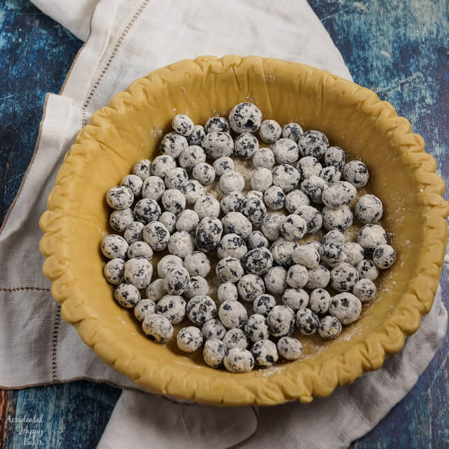 Flour dusted blueberries are added to the pie crust.