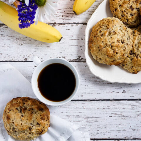 A plate of scones with a cup of coffee.