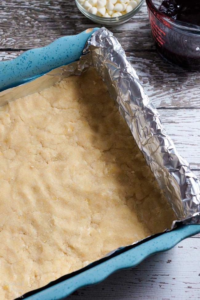 First a layer of shortbread dough is pressed into a foil lined pan.