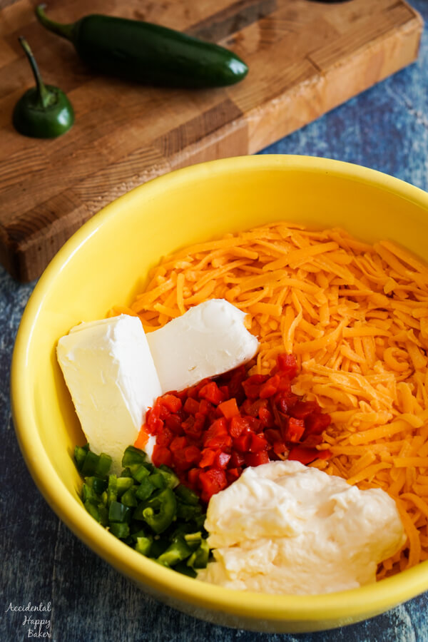 Sharp cheddar, cream cheese, may, pimentos and jalapenos in a bowl.