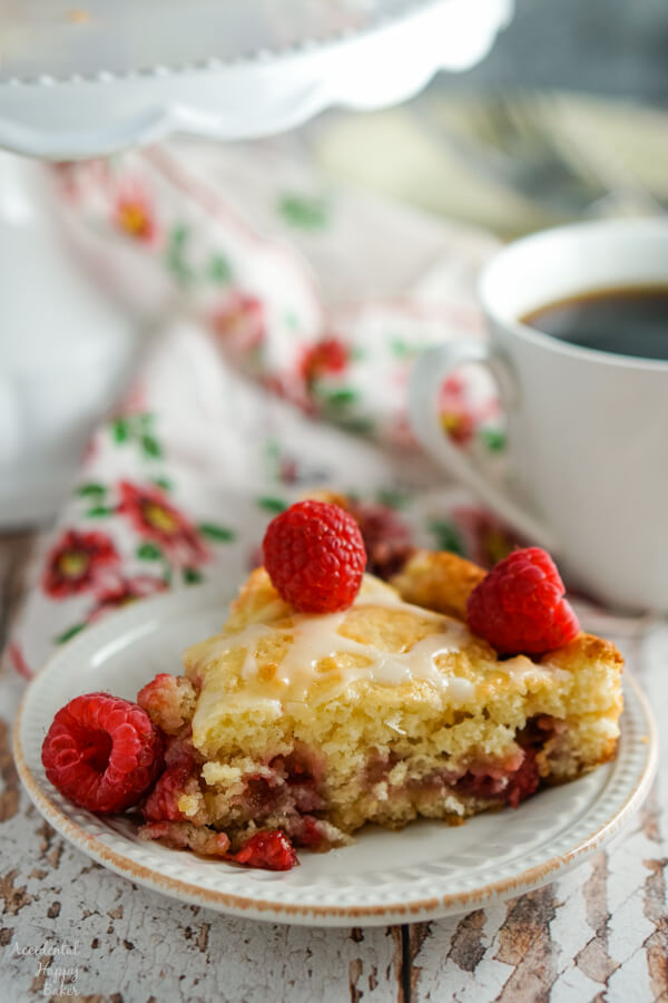 A slice of raspberry coffee cake sitting next to a cup of coffee.