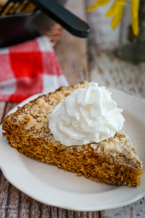 A slice of Molasses Skillet Cake on a plate, topped with a dollop of whipped cream.