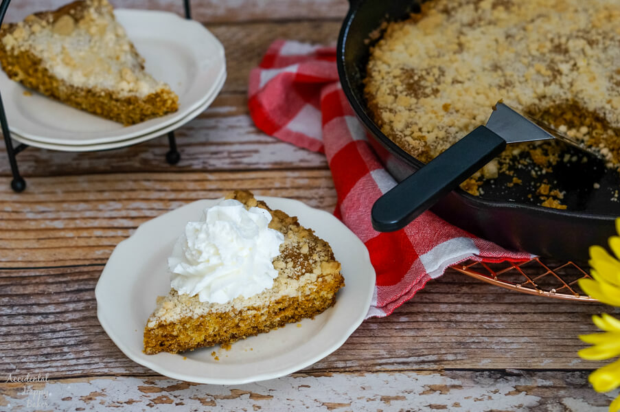 A slice of Molasses Skillet Cake with whipped cream sits next to a cast iron skillet.
