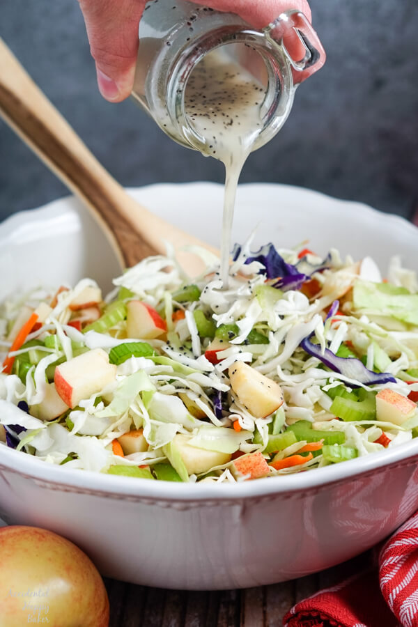 A homemade poppy seed dressing is poured over the apple coleslaw