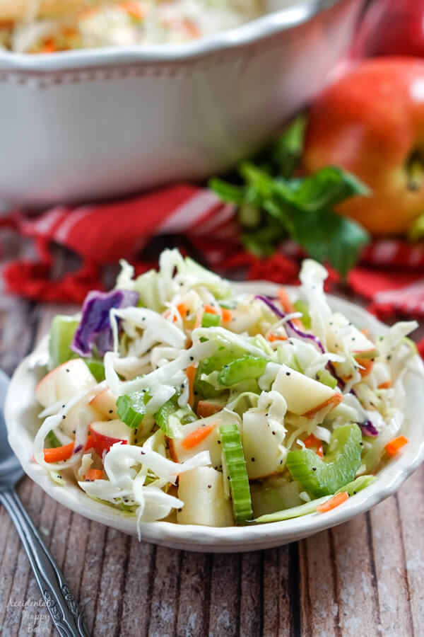 Shredded cabbage, celery, and apples mixed with homemade poppyseed dressing in a small bowl.