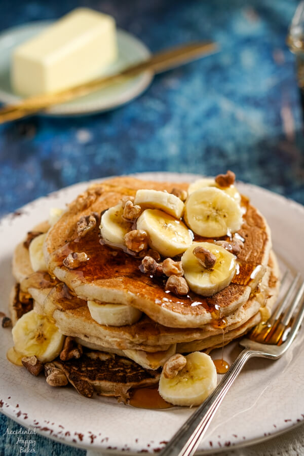 A stack of banana pancakes topped with sliced bananas, toasted walnuts, and maple syrup