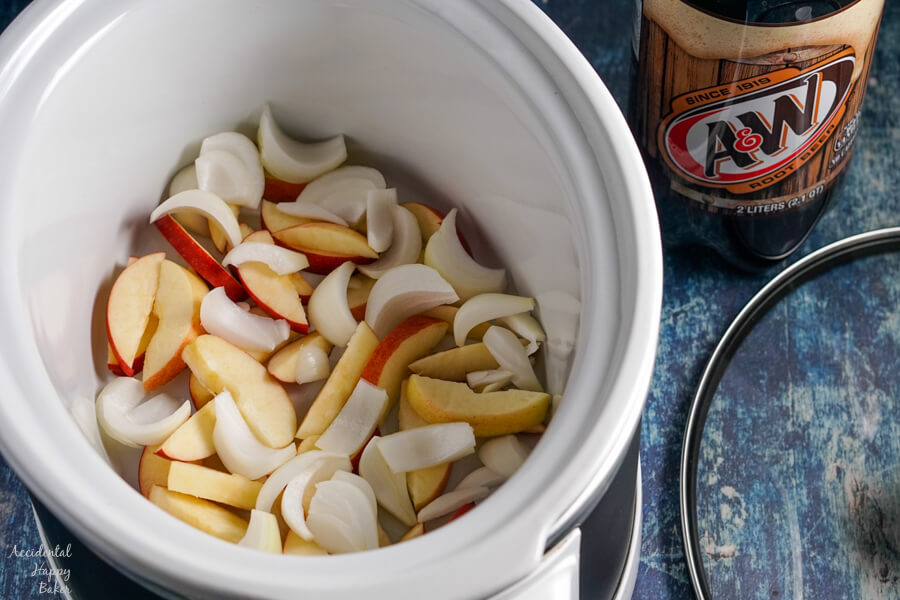 Sliced apples and onions are layered in the bottom of the slow cooker.
