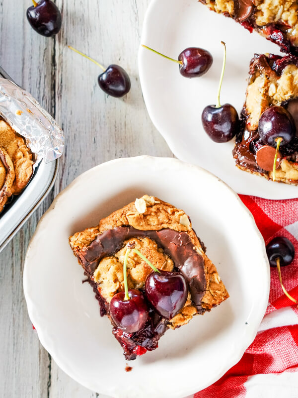 A cherry revel bar on a white plate surrounded by fresh cherries.
