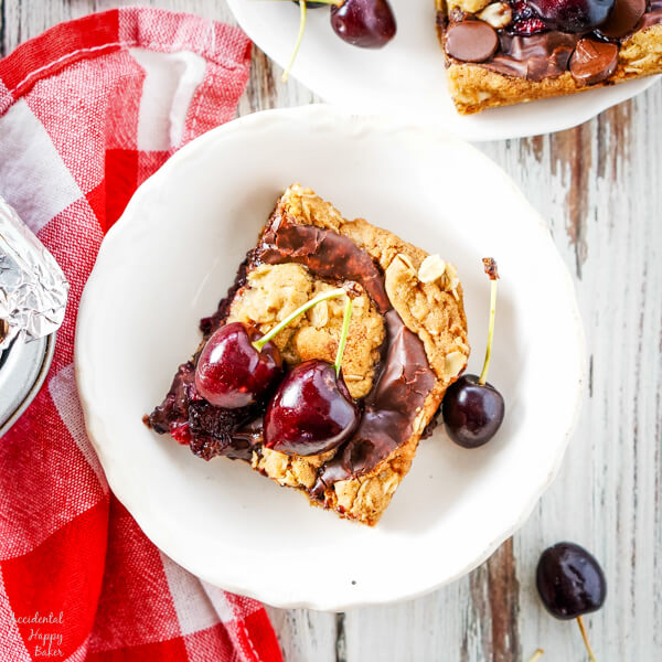 A close up of a cherry revel bar on a white plate surrounded by fresh cherries.