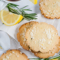 Lemon Rosemary cookies, lemon slices and rosemary sprigs are spread on a white cloth napkin beside a cup of tea.