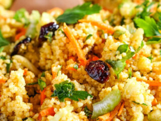 A closeup shot of curried couscous salad in a blue bowl with a wooden spoon.