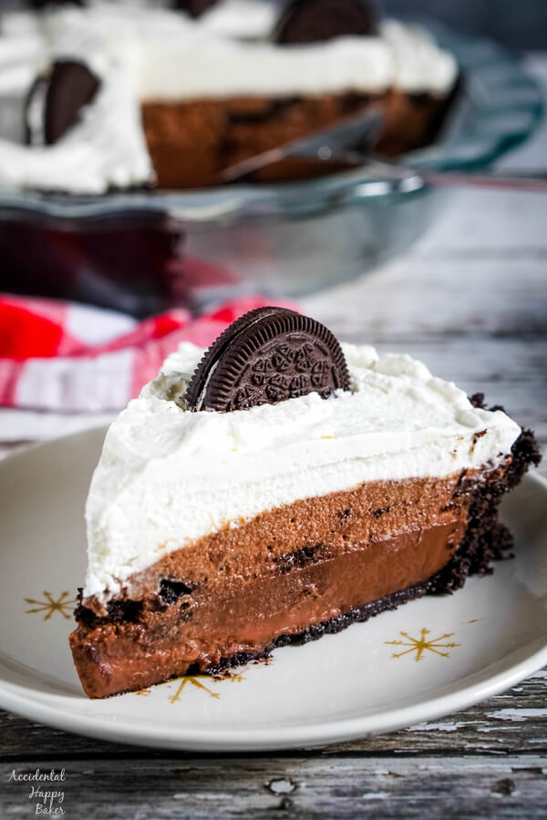 A slice of layered chocolate Oreo pie on a white plate.