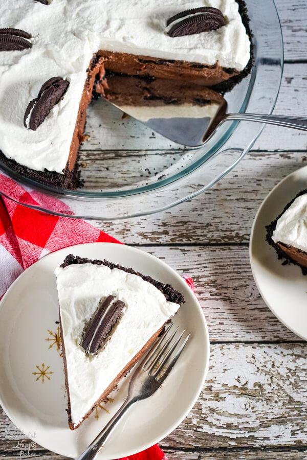 Several slices of chocolate oreo pie surround a pie plate full of chocolate oreo pie.