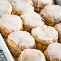 A close up on a baking pan full of cinnamon raisin biscuits.