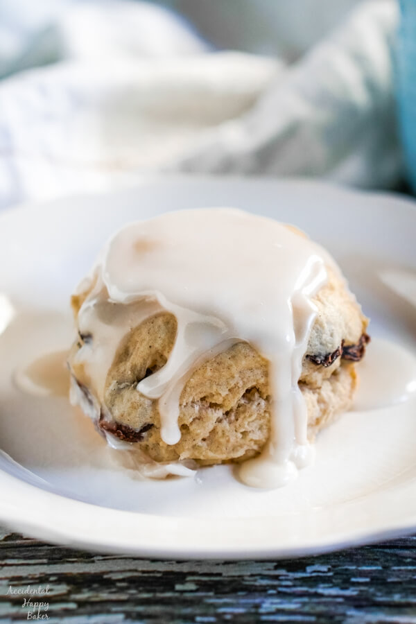 A cinnamon raisin biscuit, covered with creamy vanilla glaze on a white plate.