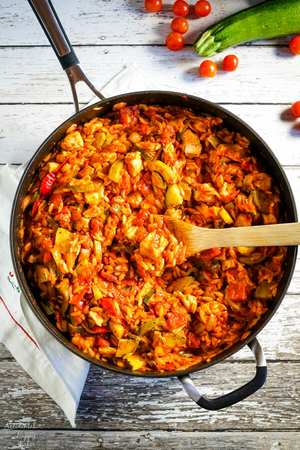 A skillet full of Italian Chicken and Orzo with a wooden spoon and zucchini and tomatoes in the background.