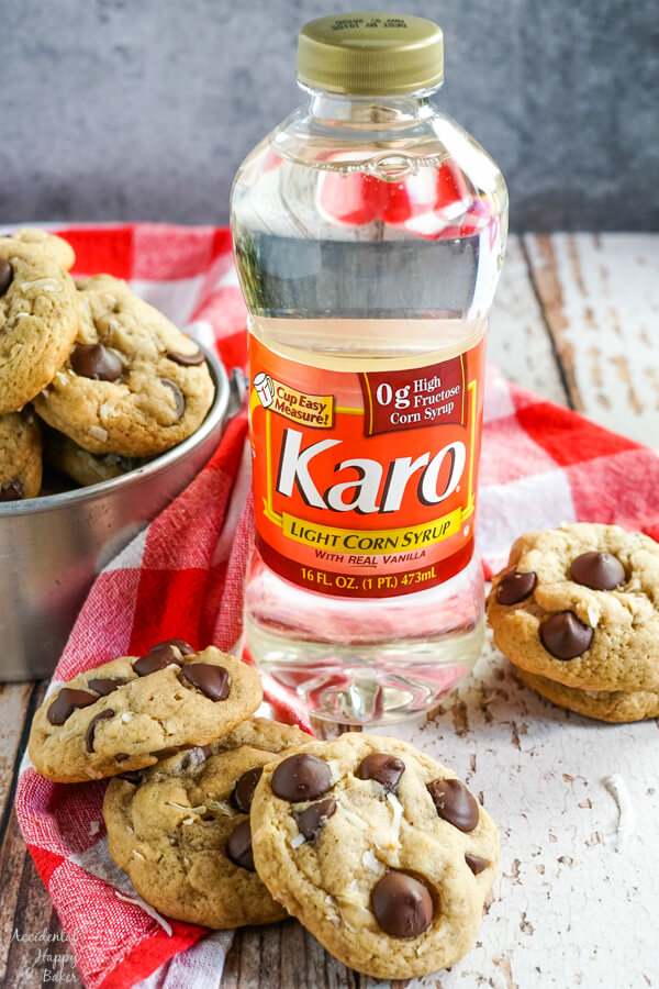 A stack of coconut chocolate chip cookies sits next to a bottle of Karo Corn Syrup