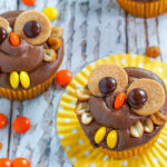 Two peanut butter chocolate owl cupcakes sit on a yellow cupcake wrappers surrounded by Reese's Pieces candy.
