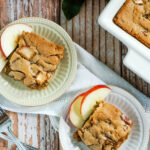 2 plates with slices of apple cinnamon bars sit next to two forks and a pan of apple cinnamon bars.