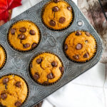 A muffin tin full of freshly baked pumpkin muffins with chocolate chips.