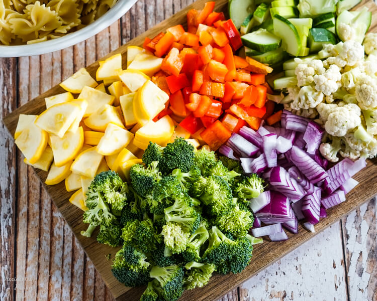 A wooden cutting board loaded with chopped yellow squash, red bell pepper, cucumber, broccoli, red onion, and cauliflower.