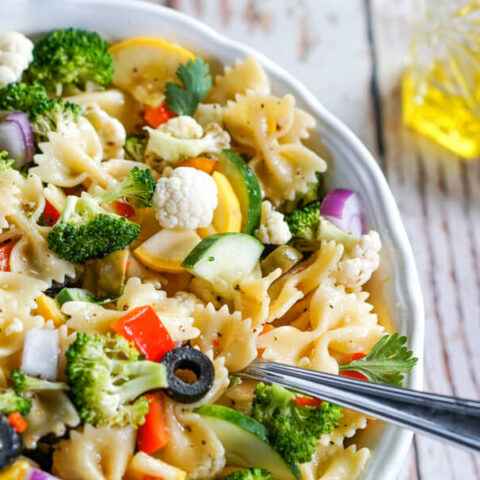 Summer vegetables and farfelle pasta tossed with an Italian dressing in a white bowl.