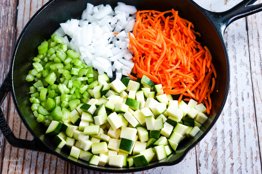 Zucchini, carrots, onions, and celery in a cast iron skillet.