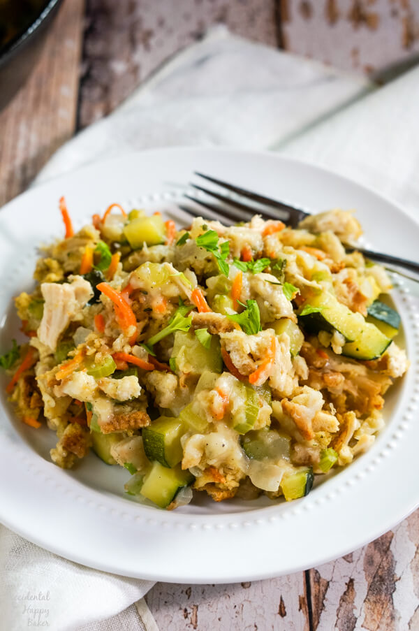A white plate with a serving of Chicken Zucchini Casserole sits on top of a cloth napkin on a table.