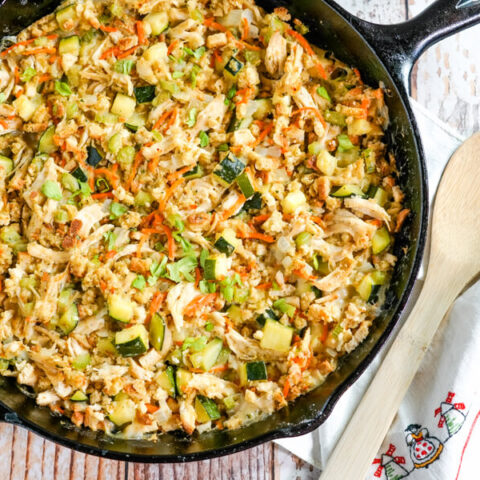 A cast iron skillet full of Chicken Zucchini Casserole sits next to a wooden spoon.