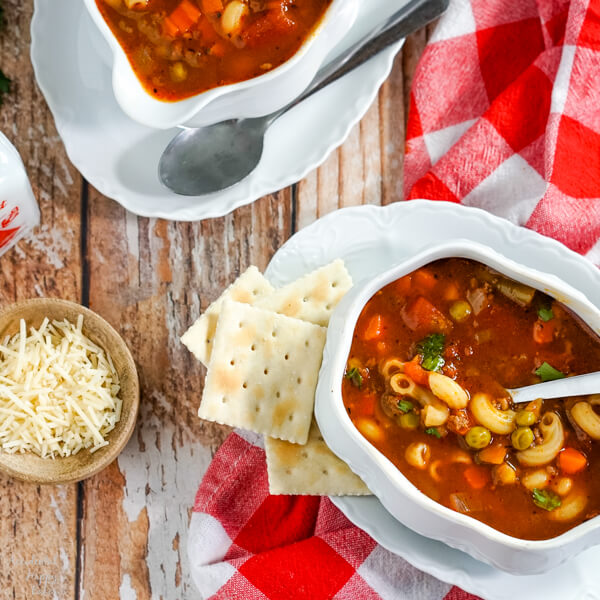 Two bowls of Hamburger Macaroni Soup sitting on a wooden table with crackers and cheese set nearby.