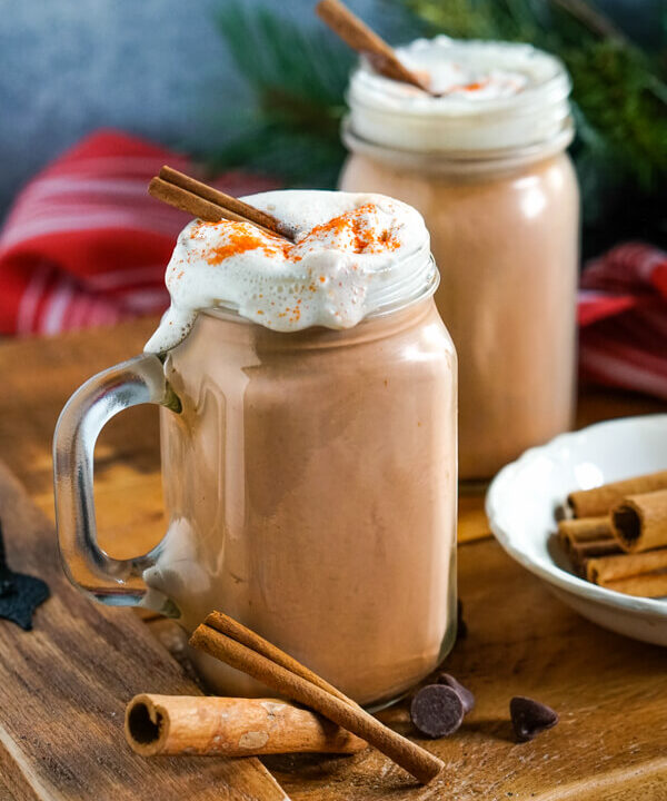 Clear glass mugs of Mexican Hot Cocoa topped with whipped cream and cinnamon sticks on a wooden tray.