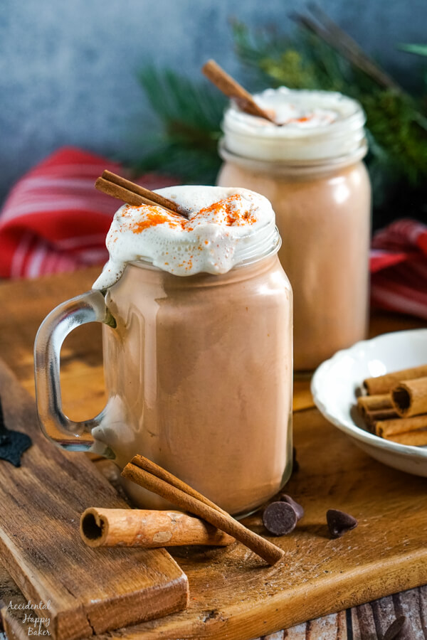 Two mugs of hot cocoa on a serving tray with cinnamon sticks.