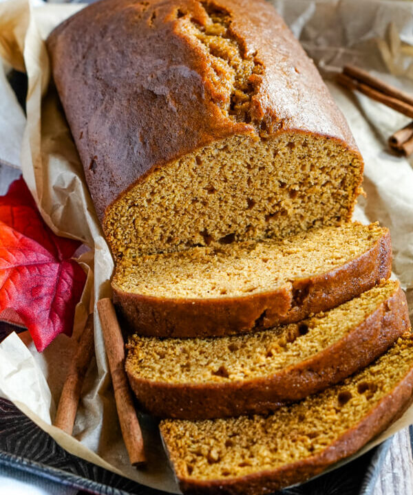 A loaf of Downeast Maine Pumpkin Bread, sliced and sitting on a baking tray.