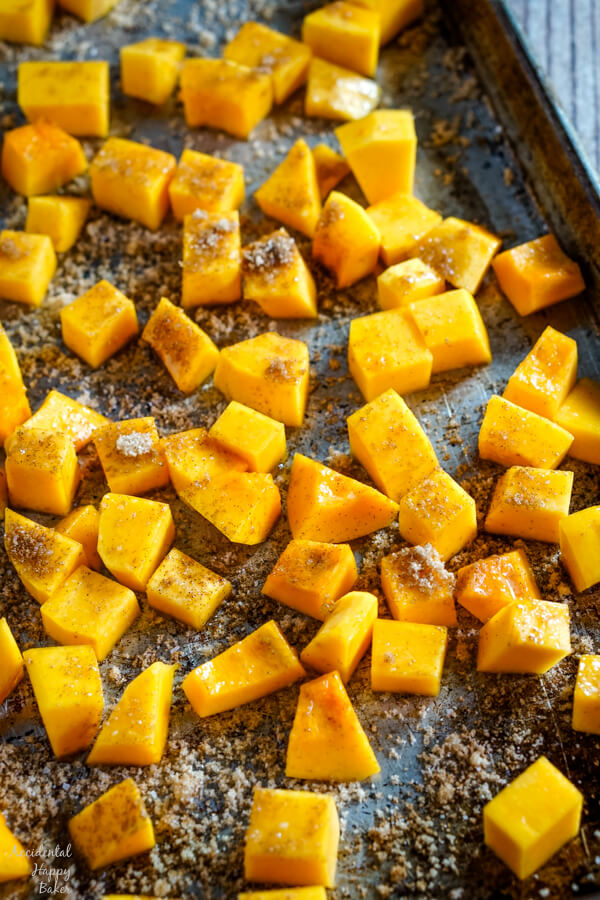 A baking sheet full of bourbon and cinnamon butternut squash ready to be placed in the oven.