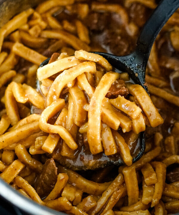 A ladle dishing out a serving of Beef and Noodles from the Instant Pot.