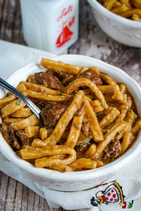 A white bowl full of beef and noodles on top of a white cloth napkin.