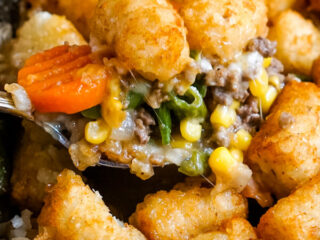 A spoonful of Shepherd's Pie with Tater Tots is scooped out of the skillet.