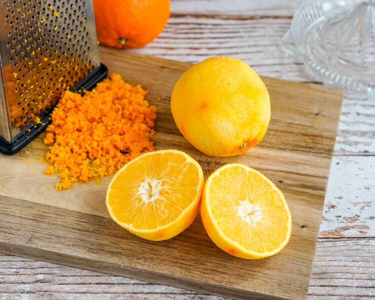 Two zested oranges on a cutting board.